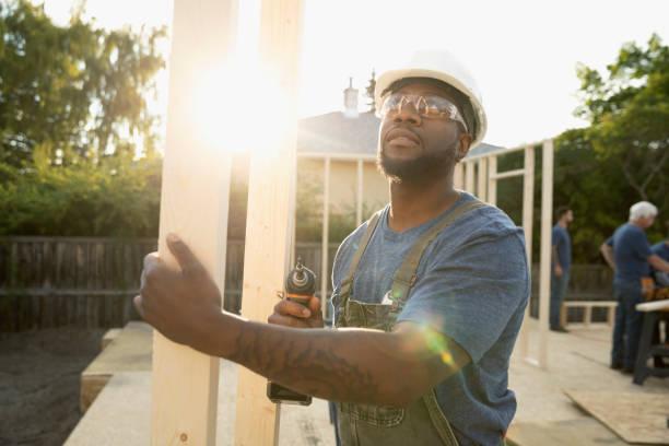 Constructeur qui porte une structure en bois sur un chantier zéro déchet