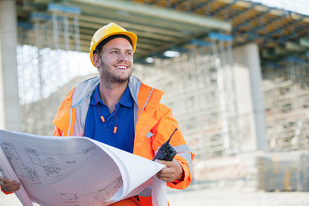 Constructeur en tenue de chantier qui tient un plan de construction