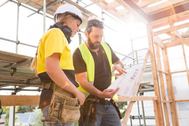 Deux constructeurs qui consultent un plan sur un chantier