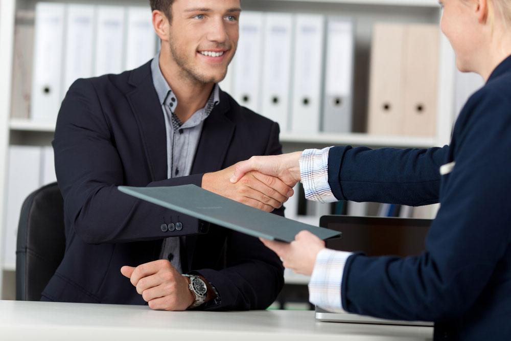 deux personnes assises de part et d'autre d'un bureau se serrent la main l'un tien un dossier dans la main